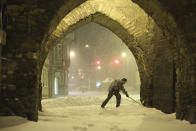 A resident shovels snow under an archway in Wernigerode, Germany, early Sunday morning, Feb. 7, 2021. Low Tristan has caused huge amounts of snow in the Harz mountains, like here in Wernigerode. (Matthias Bein/dpa via AP)