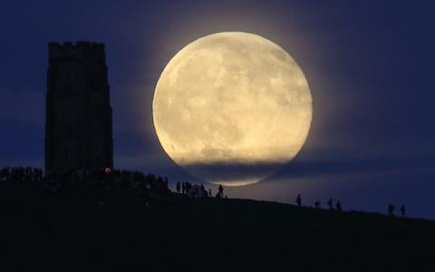 The so-called 'Strawberry Moon' rises behind Glastonbury Tor on in June 2016.  - Credit: Matt Cardy/Getty Images