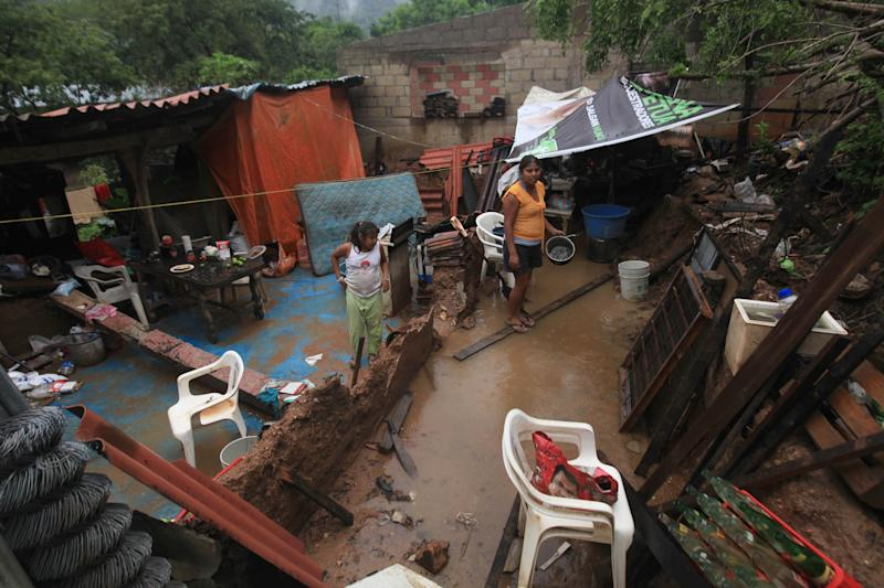 The Campos family stands in what is left of their home after it was damaged by rain triggered by Hurricane Raymond in the community of Papa Gallo de Tierra Colorada, near Acapulco, Mexico, Tuesday, Oct. 22, 2013. Hurricane Raymond weakened to barely a Category 1 storm Tuesday while still stalled off Mexico's Pacific coast, pumping rain onto an already sodden region recovering from a battering by a tropical storm last month. (AP Photo/Marco Ugarte)