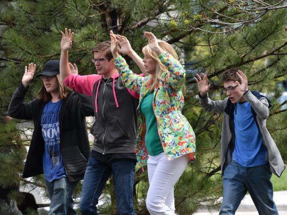 Students and teachers raise their arms as they flee a shooting at Stem School Highlands Ranch near Denver (Getty Images)