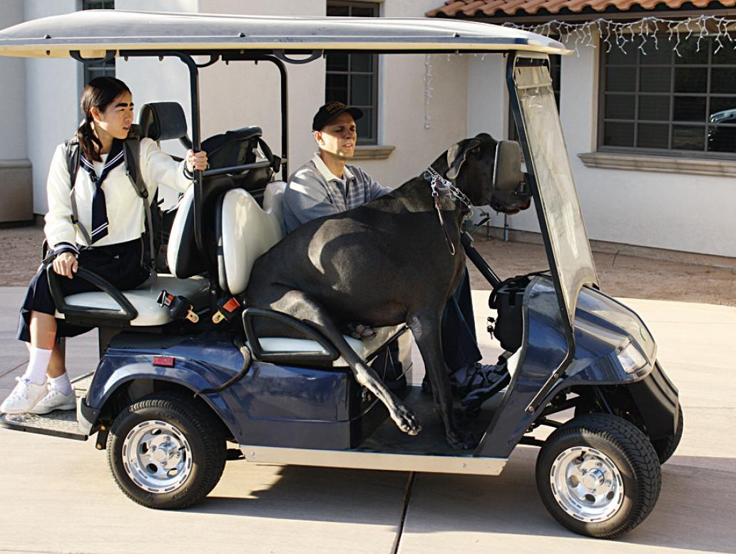 George gets a lift in a golf cart.