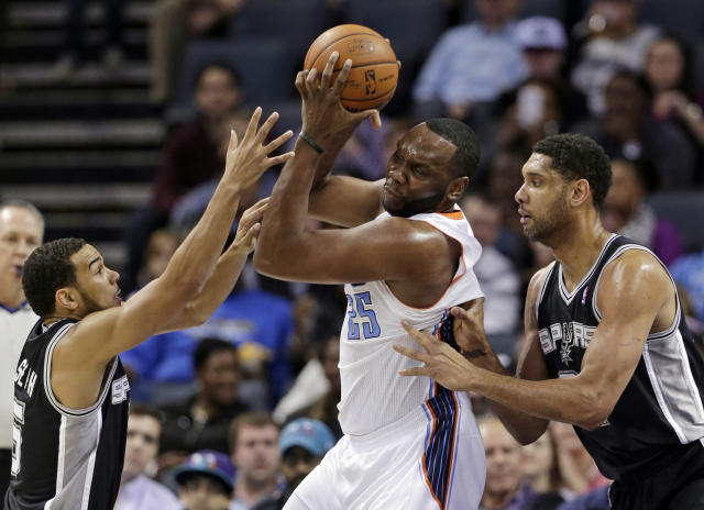 Charlotte Bobcats' Al Jefferson, center, is trapped by San Antonio Spurs' Tim Duncan, right, and Cory Joseph, left, during the first half of an NBA basketball game in Charlotte, N.C., Saturday, Feb. 8, 2014. (AP Photo/Chuck Burton)