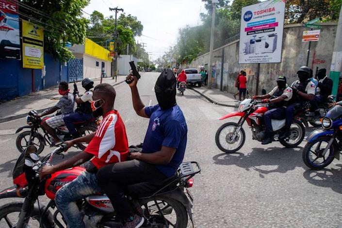 """Haiti National Police officers hold up their weapons as they protest for better working conditions and the release of jailed officers in Port-au-Prince, Haiti, Monday, Sept. 14, 2020. The protest was called for by a nationwide police group called """"Fantom 509,"""" which is associated with the police union."""