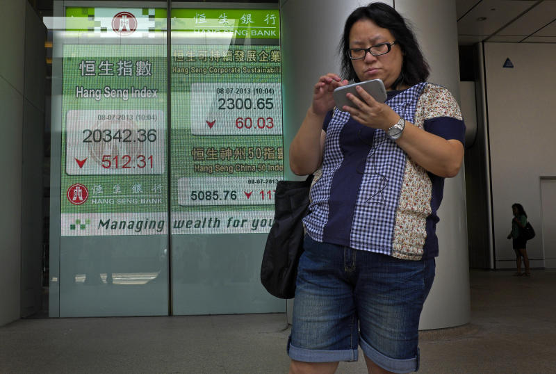 A woman stands in front of electronic board showing the Hong Kong share index outside a local bank in Hong Kong, Monday, July 8, 2013. Concern over China's slowdown weighed on Asian stock markets Monday after the head of the International Monetary Fund warned of a loss of momentum in emerging economies. Asia's losses came despite strong U.S. job numbers that sparked a Wall Street rally on Friday. Hong Kong's Hang Seng dropped 1.9 percent to 20,463.80 at the midday close. (AP Photo/Vincent Yu)