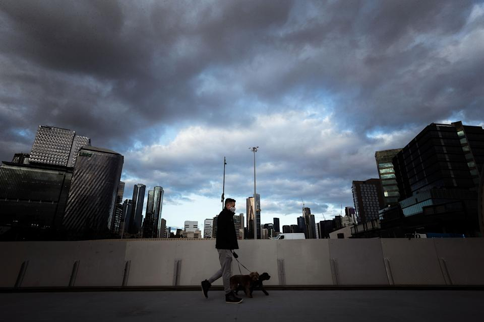 A Melbourne man walks his dog under strict Stage 4 restrictions. Source: Getty