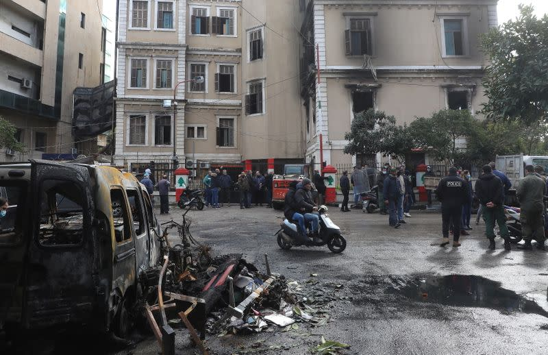 People gather at the municipality building that was set ablaze overnight, in the aftermath of protests against the lockdown and worsening economic conditions, amid the spread of the coronavirus disease (COVID-19), in Tripoli