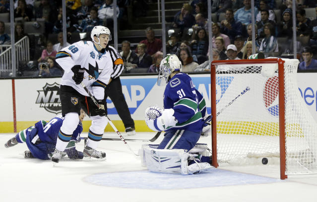 San Jose Sharks center Tomas Hertl (48) scores past Vancouver Canucks goalie Eddie Lack, right, during the first period of a preseason NHL hockey game on Tuesday, Sept. 24, 2013, in San Jose, Calif. (AP Photo/Marcio Jose Sanchez)