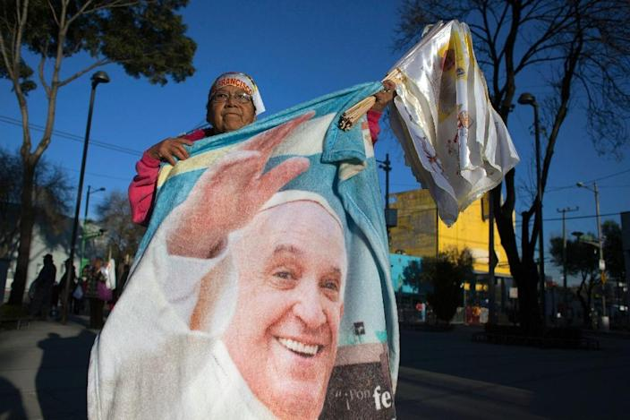 A woman shows a blanket with the image of Pope Francis in the streets of Mexico City on February 13, 2016 (AFP Photo/Antonio Nava)