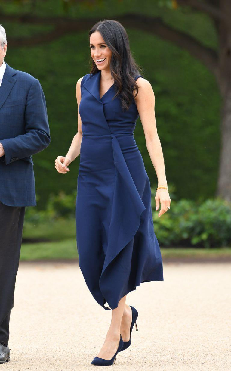 """<p>In Melbourne for a reception at Government House, the expectant mother wore a navy blue <a href=""""https://www.net-a-porter.com/us/en/Shop/Designers/Dion_Lee/Clothing?cm_mmc=LinkshareUK-_-TnL5HPStwNw-_-Custom-_-LinkBuilder&siteID=TnL5HPStwNw-fLTdDQYhP9irXvaXT9apfw&Skimlinks.com=Skimlinks.com&dclid=CKC9_-joj94CFTMe0wodnFcG5w&pn=1&npp=60&image_view=product&dScroll=0"""" rel=""""nofollow noopener"""" target=""""_blank"""" data-ylk=""""slk:Dion Lee"""" class=""""link rapid-noclick-resp"""">Dion Lee</a> dress, called the 'folded sail dress'. The Duchess paired the sleek dress with navy Manolo Blahnik BB pumps, (which are sold out, but <a href=""""https://www.farfetch.com/uk/shopping/women/manolo-blahnik-bb-pumps-item-13103173.aspx?pid=stylight.co.uk&af_channel=affiliate&is_retargeting=true"""" rel=""""nofollow noopener"""" target=""""_blank"""" data-ylk=""""slk:these are similar"""" class=""""link rapid-noclick-resp"""">these are similar</a>) a <a href=""""https://shaunleane.com/collections/bracelets/products/silver-and-yellow-gold-diamond-signature-cuff-medium"""" rel=""""nofollow noopener"""" target=""""_blank"""" data-ylk=""""slk:gold cuff bracelet by Shaun Lane"""" class=""""link rapid-noclick-resp"""">gold cuff bracelet by Shaun Lane</a>, as well as a <a href=""""https://www.net-a-porter.com/gb/en/Shop/Designers/Gucci/Bags?pn=1&npp=60&image_view=product&dScroll=0"""" rel=""""nofollow noopener"""" target=""""_blank"""" data-ylk=""""slk:Gucci"""" class=""""link rapid-noclick-resp"""">Gucci</a> <a href=""""https://www.farfetch.com/uk/shopping/women/gucci-sylvie-leather-shoulder-bag-item-11973129.aspx?storeid=10524&size=17&pid=googleadwords_int&af_channel=Search&c=629762120&af_c_id=629762120&af_keywords=pla-383851892833&af_adset_id=48630141311&af_ad_id=217936576764&is_retargeting=true&shopping=yes&gclid=EAIaIQobChMIr9XFzPCP3gIVDD0MCh2bNgfbEAYYAiABEgKTd_D_BwE"""" rel=""""nofollow noopener"""" target=""""_blank"""" data-ylk=""""slk:Sylvie bag"""" class=""""link rapid-noclick-resp"""">Sylvie bag</a>. Ever the clever packer, the former actress also re wore the classic trench she donned on her first day in the country"""