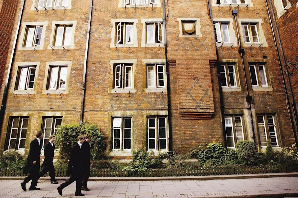 <p>Pupils at Eton College hurry between lessons, wearing the school uniform of tailcoats and starched collars</p> (Getty Images)