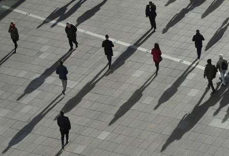 FILE PHOTO: People cast long shadows in the winter sunlight as they walk across a plaza in the Canary Wharf financial district of London