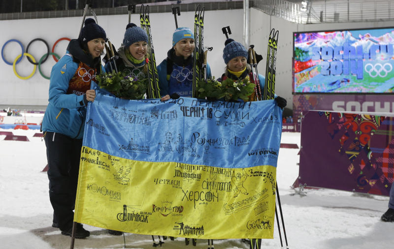 Ukraine's relay team Vita Semerenko, Juliya Dzhyma, Olena Pidhrushna and Valj Semerenko, from left, celebrate with Ukrainian flag with writings on it after winning the gold during the flower ceremony of the women's biathlon 4x6k relay at the 2014 Winter Olympics, Friday, Feb. 21, 2014, in Krasnaya Polyana, Russia. (AP Photo/Kirsty Wigglesworth)