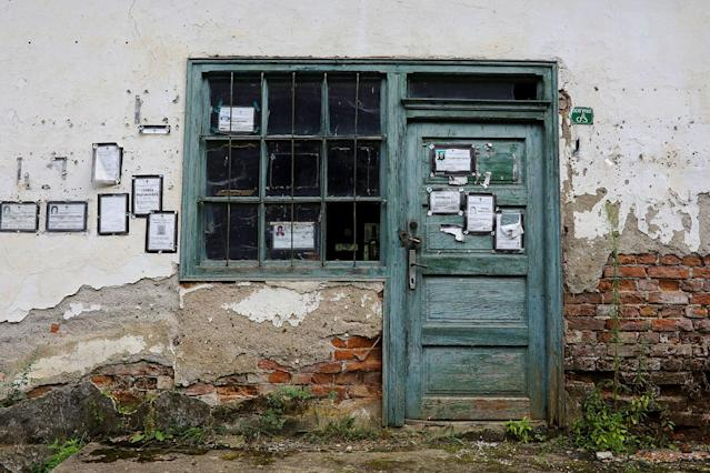 <p>Death notices are seen on the door and the wall of a closed shop in the village of Papratna, near the southeastern town of Knjazevac, Serbia, Aug. 14, 2017. (Photo: Marko Djurica/Reuters) </p>