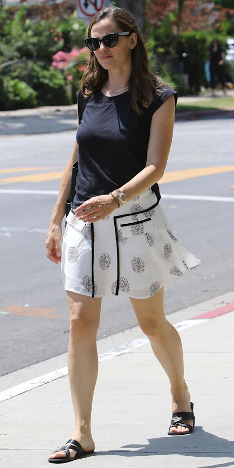 <p>Jen headed to church in Brentwood on Sunday in her go-to semi-casual ensemble: a black tee and her beloved patterned skirt with black piping, a pair of flat sandals and shades thrown in the mix. </p>