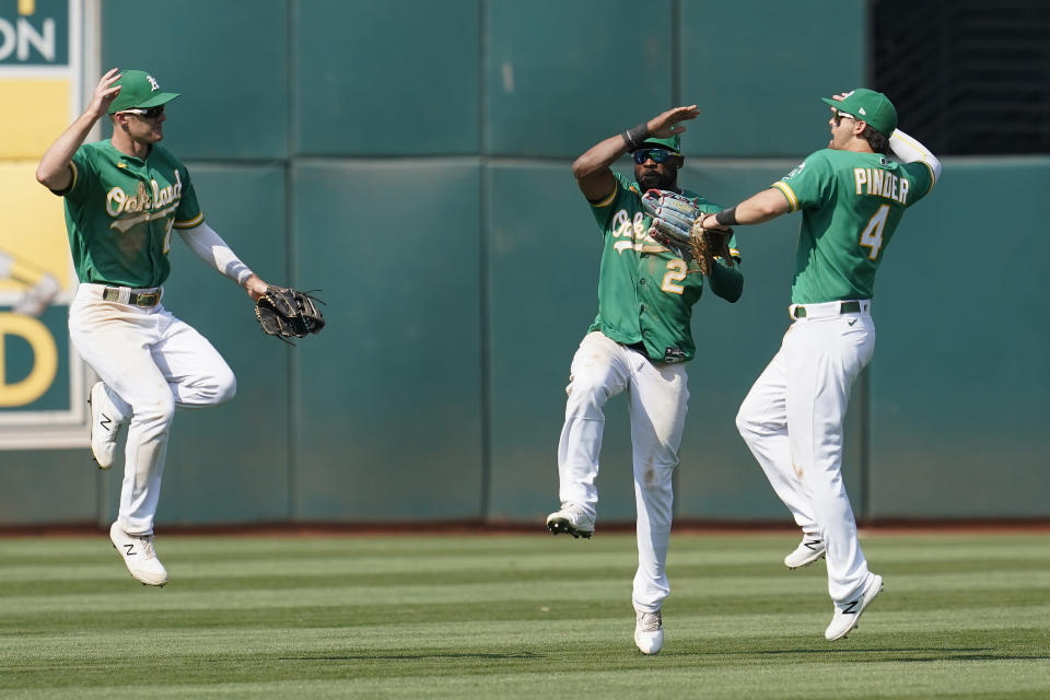 From left to right, Oakland Athletics' Mark Canha, celebrates with Starling Marte and Chad Pinder after they defeated the New York Yankees in a baseball game in Oakland, Calif., Saturday, Aug. 28, 2021. (AP Photo/Jeff Chiu)
