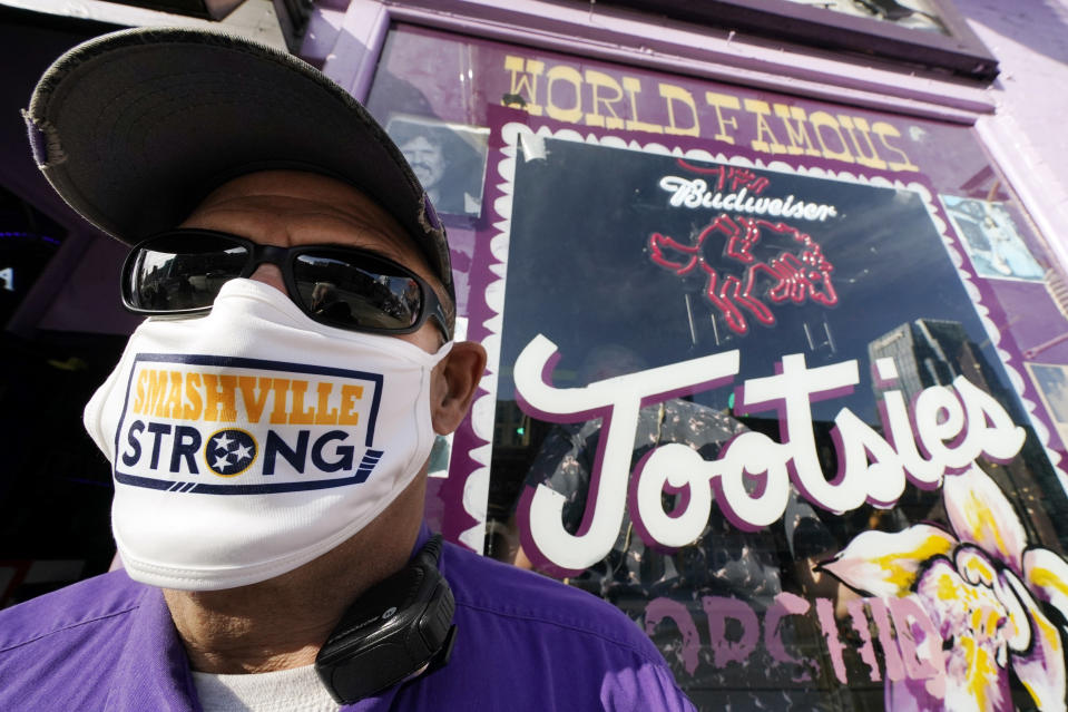 Jeffrey Susan, a security guard at Tootsies Orchid Lounge, wears a Nashville Strong face mask as he stands outside the famous honky-tonk Tuesday, Dec. 29, 2020, in Nashville, Tenn. The Christmas Day explosion near the center of the tourist area has sparked shock across the city and the country. Officials have named 63-year-old Anthony Quinn Warner as the man behind the Christmas Day explosion in which he was killed, but the motive has remained elusive. (AP Photo/Mark Humphrey)