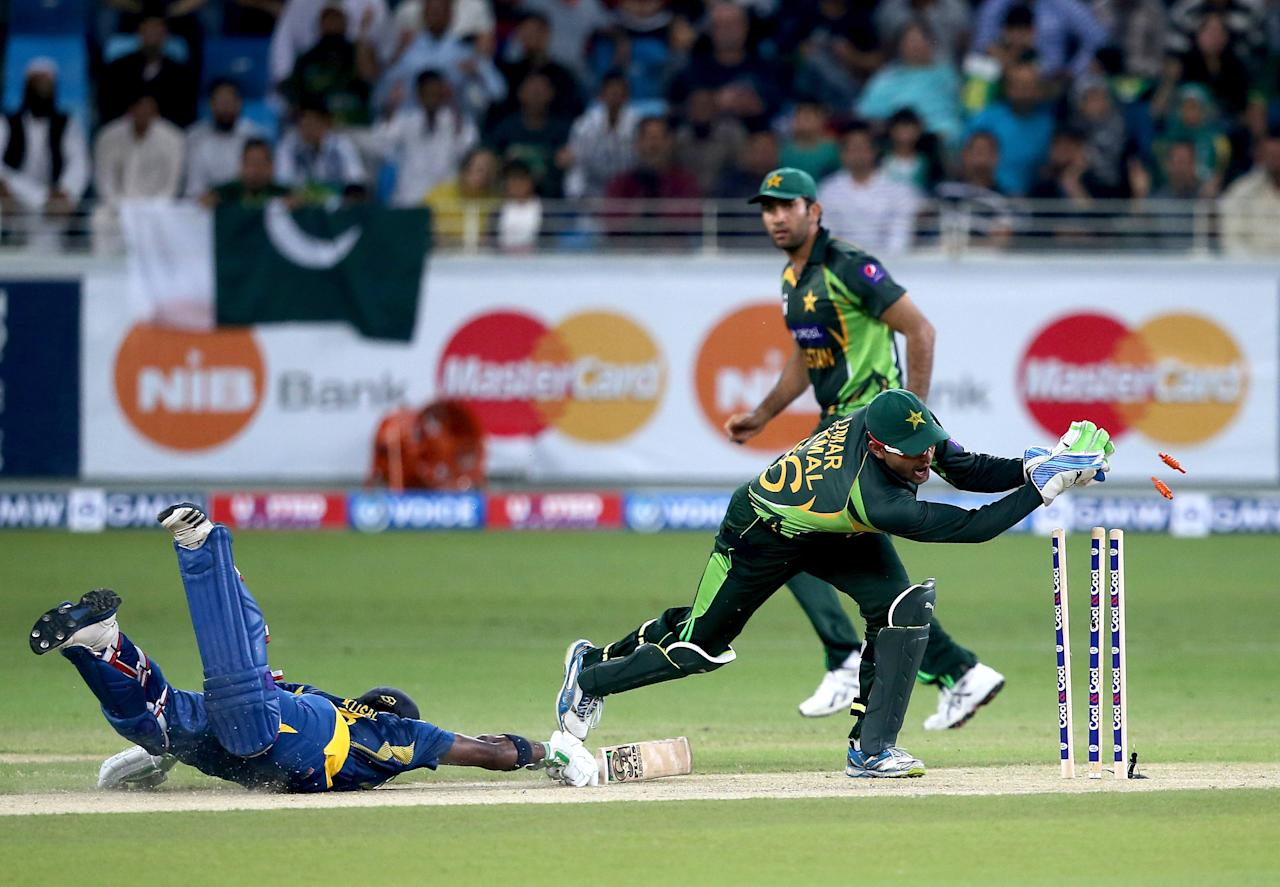 DUBAI, UNITED ARAB EMIRATES - DECEMBER 13:  Kusal Janith Perara (L) of Sri Lanka survives a run out attempt by Umar Akmal (R) of Pakistan during the second Twenty20 International match between Pakistan and Sri Lanka at Dubai Sports City Cricket Stadium on December 13, 2013 in Dubai, United Arab Emirates.  (Photo by Francois Nel/Getty Images)