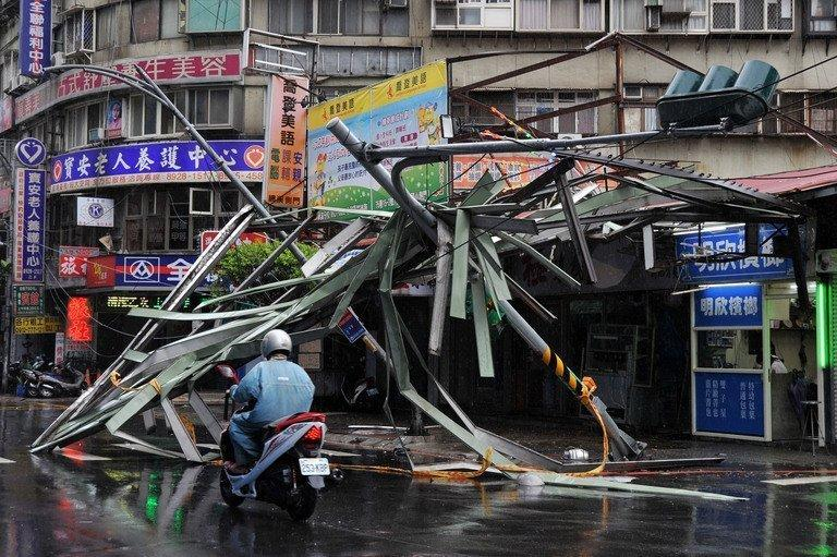 A motorcycle drives past a damaged tin roof and traffic signs, caused by typhoon Soulik, in Taipei, on July 13, 2013. Soulik has battered Taiwan with torrential rain and powerful winds that left two people dead and at least 100 injured