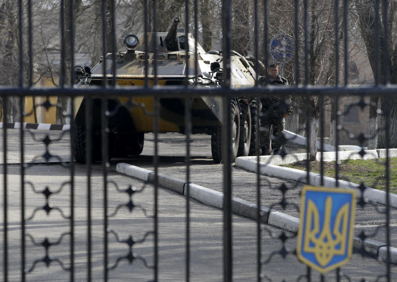 A Ukrainian armored personnel carrier is stationed behind the gate of a military base in the port of Kerch, Ukraine, Monday, March 3, 2014. Pro-Russian troops controlled a ferry terminal on the easternmost tip of Ukraine's Crimea region close to Russia on Monday, intensifying fears that Moscow will send even more troops into the strategic Black Sea region in its tense dispute with its Slavic neighbor. (AP Photo/Darko Vojinovic)