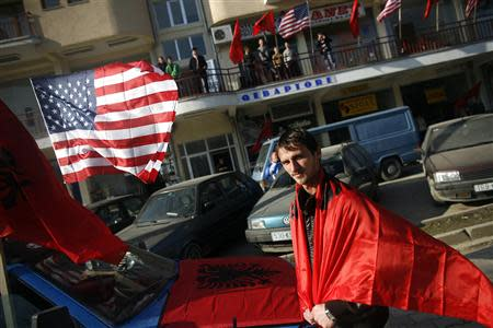 An ethnic Albanian man is seen wrapped in the Albanian flag in celebration for the province's upcoming independence, in the village of Suva Reka in Kosovo, in this February 15, 2008 file photo. REUTERS/Damir Sagolj/Files