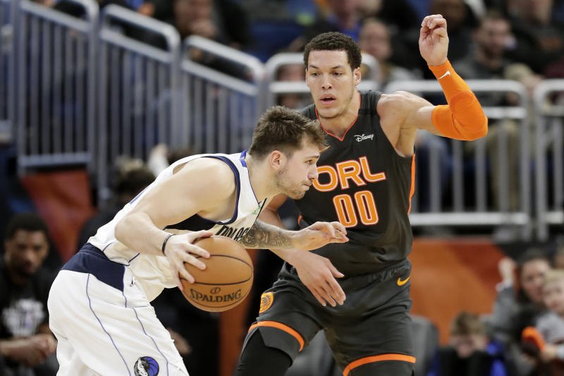 Dallas Mavericks guard Luka Doncic, left, drives around Orlando Magic forward Aaron Gordon (00) during the second half of an NBA basketball game, Friday, Feb. 21, 2020, in Orlando, Fla. (AP Photo/John Raoux)