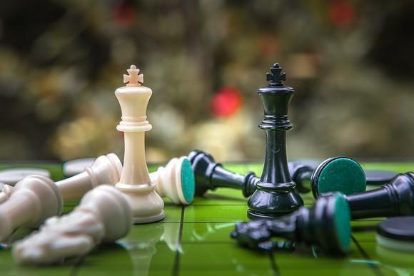 Two chess piece kings facing each other while other chess pieces are scattered around them
