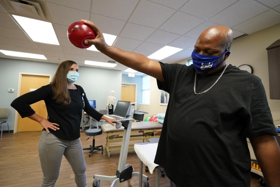 Emily Smith watches as Larry Brown lifts a weighted ball during an occupational therapy session at Community Health Network, Thursday, Aug. 20, 2020, in Indianapolis. He didn't die of COVID-19, but he's coming to terms with the fact that his life might never be the same. (AP Photo/Darron Cummings)