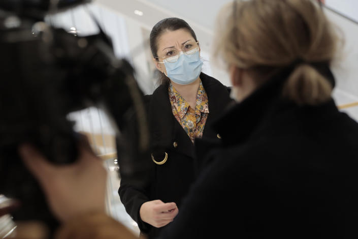 Plaintiff Sabrina Deliry answers reporters before the start of a hearing at the Paris Palace of Justice, Wednesday, March 3, 2021. A Paris court holds a hearing Wednesday in a class-action effort to hold French health authorities and companies accountable after thousands of people with the virus died in nursing homes, and families were locked out and left in the dark about what was happening to their isolated loved ones. Sabrina Deliry has mobilized families around France since her mother's Paris nursing home was first locked down a year ago. (AP Photo/Lewis Joly)