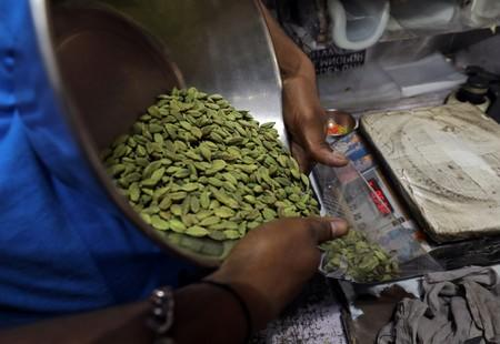 A shopkeeper packs cardamom for a customer in a market area in the old quarters of Delhi