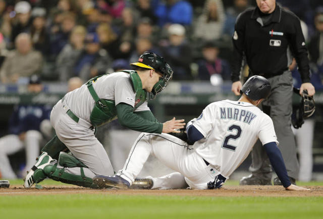 Seattle Mariners' Tom Murphy is tagged out at home by Oakland Athletics catcher Sean Murphy trying to score during the fifth inning of a baseball game, Saturday, Sept. 28, 2019, in Seattle. (AP Photo/John Froschauer)