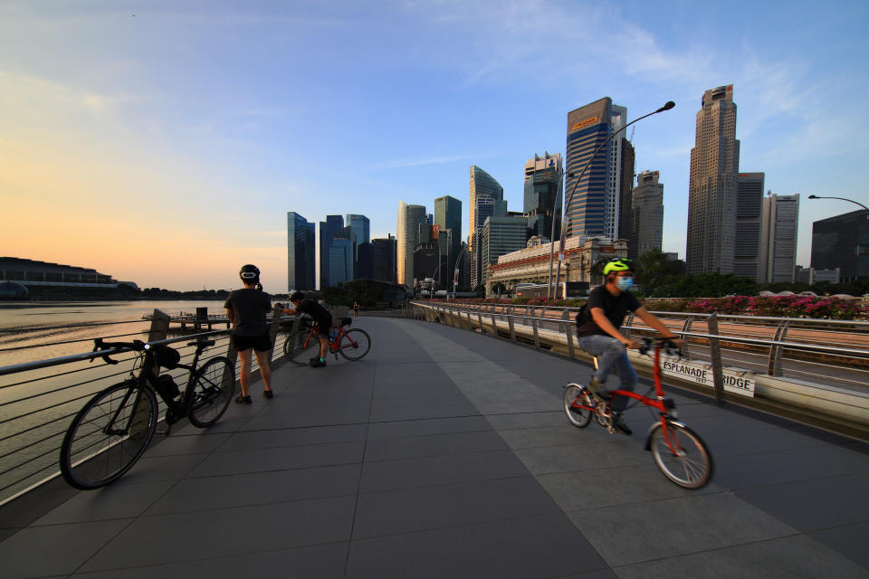 People cycle along the Jubilee Bridge with the city skyline pictured in the background at Marina Bay on February 15, 2021 in Singapore.  (Photo by Suhaimi Abdullah/NurPhoto via Getty Images)