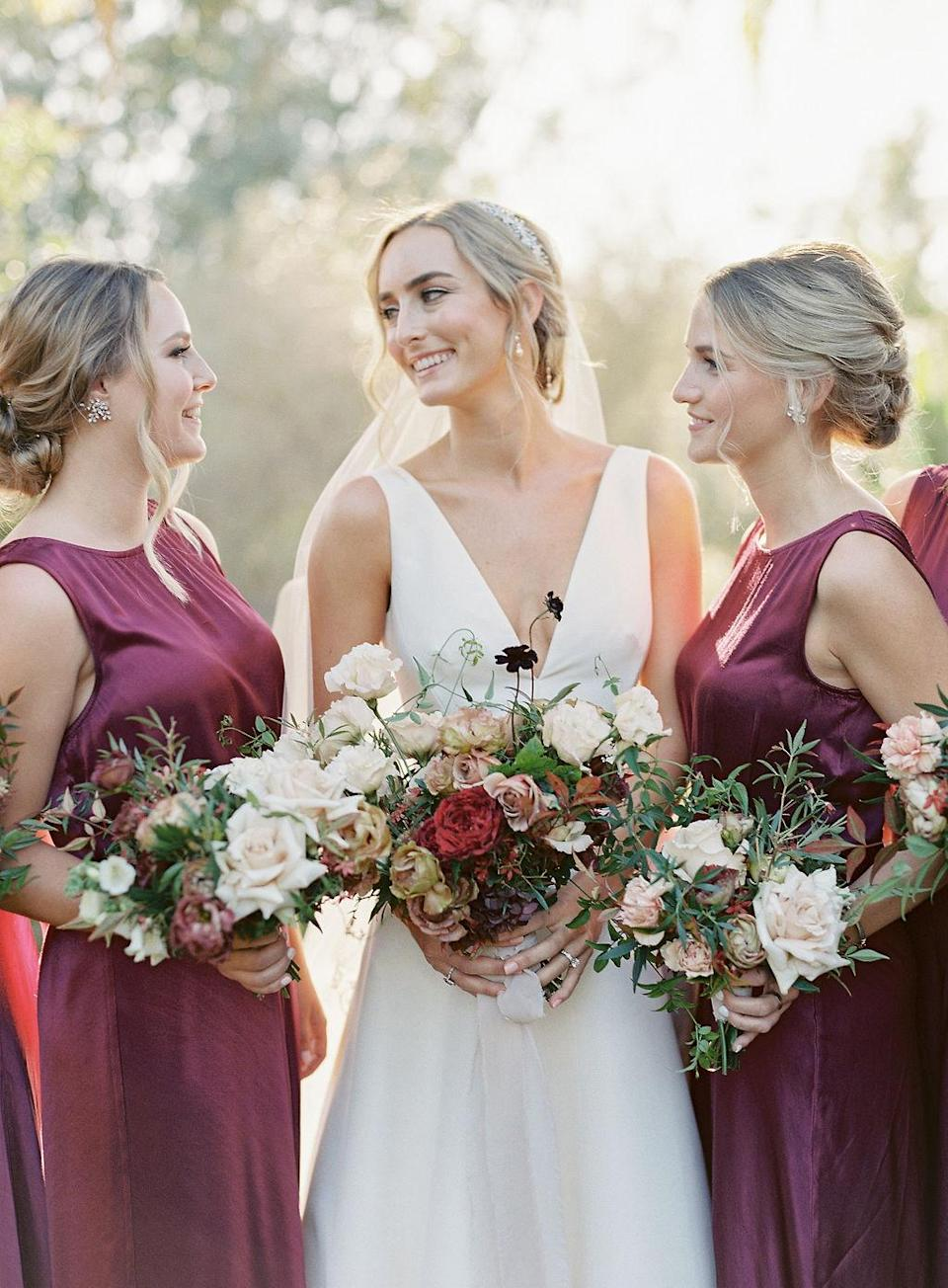 "<p>The bridesmaids wore <a href=""https://www.bhldn.com/"" rel=""nofollow noopener"" target=""_blank"" data-ylk=""slk:BHLDN"" class=""link rapid-noclick-resp"">BHLDN</a> dresses in a deep wine color. ""I wanted something classic yet still chic, an investment dress that you would see any wedding guest in potentially,"" Campbell says. ""The beautiful silk drape gave the dress old Hollywood vibes and it felt very timeless to me."" The ceremony readers and attendants wore the same boat neck dress in a champagne tone.</p> <p>Campbell held an unstructured bouquet—by florist <a href=""https://plentyofpetals.com/"" rel=""nofollow noopener"" target=""_blank"" data-ylk=""slk:Plenty of Petals"" class=""link rapid-noclick-resp"">Plenty of Petals</a>—with greenery, garden blooms, and textured foliage in tones of mauve, burgundy, and ivory. The florals included four types of roses, dahlias, hellebores, lisianthus, hydrangea, and jasmine vines; the arrangement was tied with a soft ivory silk chiffon ribbon.</p>"