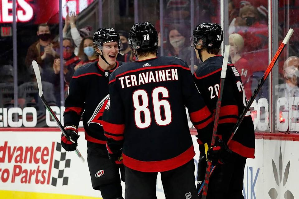 Carolina Hurricanes' Andrei Svechnikov (37) comes to celebrate with teammates Teuvo Teravainen (86) and Sebastian Aho (20) a goal by Aho during the second period of an NHL hockey game in Raleigh, N.C., Monday, May 3, 2021. (AP Photo/Karl B DeBlaker)