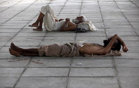 Men sleep in shade under a bridge during intense hot weather in Karachi, Pakistan, June 22, 2015.  REUTERS/Akhtar Soomro  -