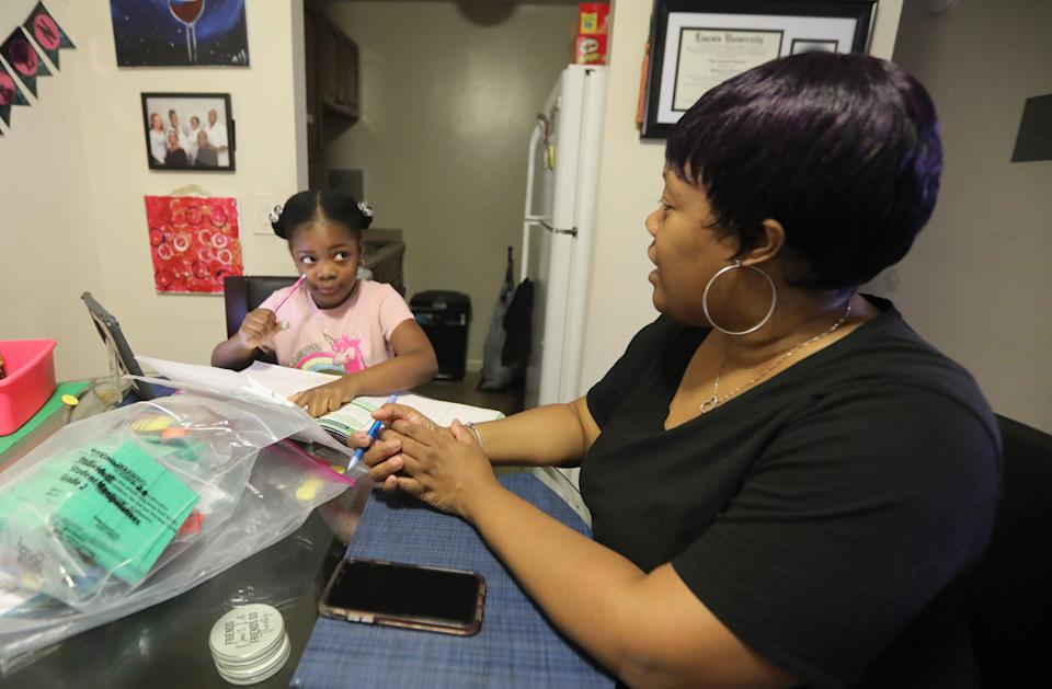 Nicole Johnson helps her daughter Khloe, 6, do school work in their White Plains home Oct. 14, 2020. Johnson, who had worked for the past eight years as a teacher's aide, was forced to give up her job in order to care for her daughter, a second-grader in the White Plains school district who is doing all virtual learning due to the COVID-19 pandemic.