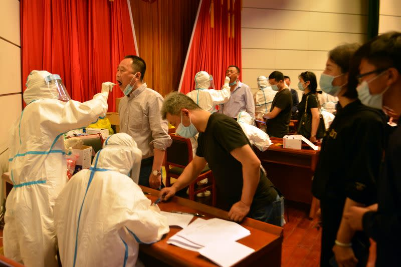 Medical workers collect swabs from residents following new cases of the coronavirus disease (COVID-19), at a nucleic acid test site in Luan, Anhui