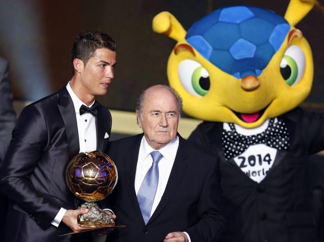 Portugal's Cristiano Ronaldo poses with FIFA President Sepp Blatter (C) and 2014 World Cup mascot Fuleco after being awarded the FIFA Ballon d'Or 2013 in Zurich January 13, 2014. Portugal and Real Madrid forward Cristiano Ronaldo was named the world's best footballer for the second time on Monday, preventing his great rival Lionel Messi from winning the award for a fifth year in a row. REUTERS/Arnd Wiegmann (SWITZERLAND - Tags: SPORT SOCCER)