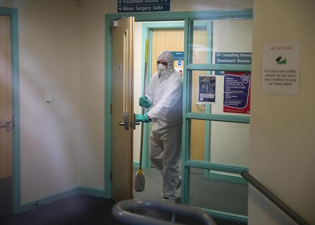 A man in protective clothing cleans the County Oak Medical Centre GP practice in Brighton after a member of staff contracted coronavirus (Getty)