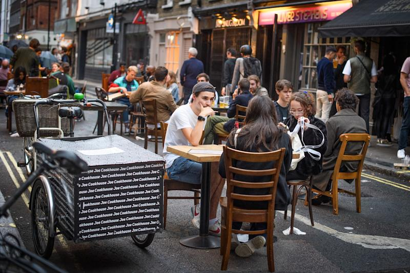 People eat and drink oudoors in Soho, London, as coronavirus lockdown restrictions are eased across England. Many streets in Soho were pedestrianised for the night, and bars and restaurants added extra outdoor seating. Picture date: Sunday July 5, 2020. Photo credit should read: Matt Crossick/Empics