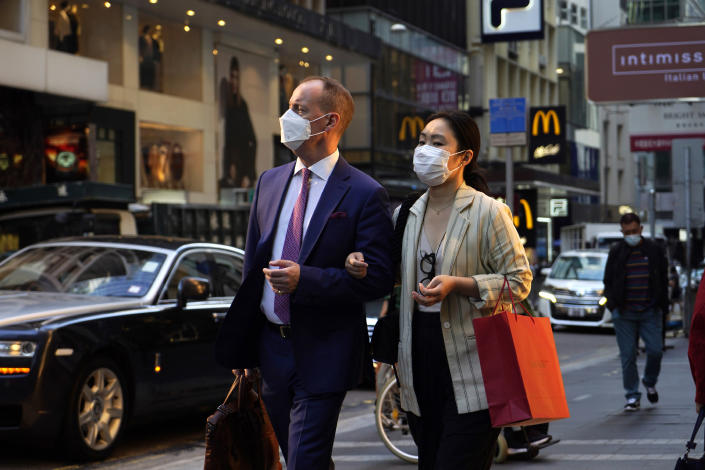 People wearing face masks to protect against the spred of the coronavirus, walk along a street in Hong Kong, Monday, Nov. 30, 2020. (AP Photo/Kin Cheung)