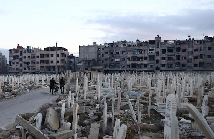 Syrian men walk in a cemetery in the rebel-held town of Douma, on the eastern outskirts of the capital Damascus on January 9, 2017 (AFP Photo/Abd Doumany)