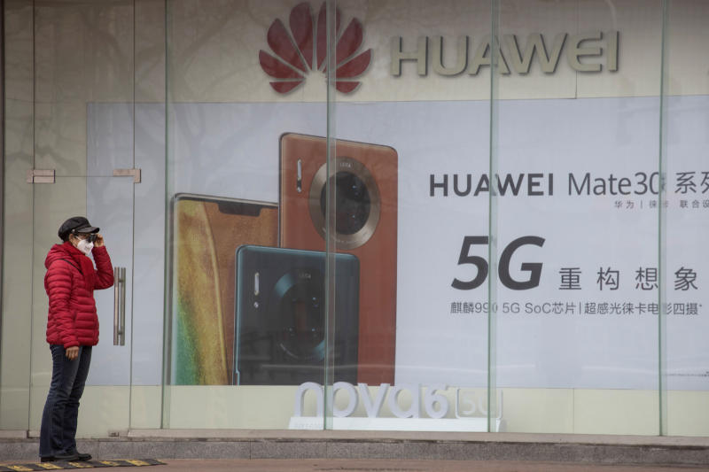 In this photo taken Sunday, March 8, 2020, a woman wearing a mask against COVID-19 stands near an advertisement for Huawei mobile phones in Beijing. Chinese tech giant Huawei says Tuesday, March 31, 2020, its 2019 sales rose 19.1% over a year earlier despite U.S. sanctions that hampered its smartphone and network equipment businesses. The company is embroiled in a series of disputes with Washington, which says Huawei is a security risk, an accusation it denies. (AP Photo/Ng Han Guan)