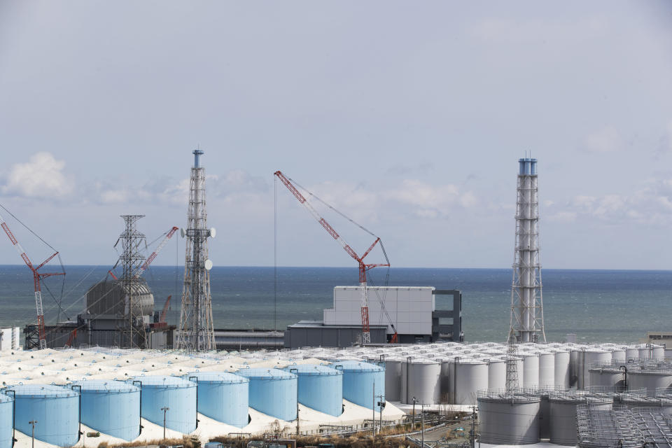 FILE - In this Feb. 27, 2021, file photo, the Pacific Ocean looks over nuclear reactor units of No. 3, left, and 4 at the Fukushima Daiichi nuclear power plant in Okuma town, Fukushima prefecture, northeastern Japan. Japan's government adopted an interim plan Tuesday, Aug. 24, 2021 that it hopes will win support from fishermen and other concerned groups for a planned release into the sea of treated but still radioactive water from the wrecked Fukushima nuclear plant. The government decided in April to start discharging the water into the Pacific Ocean in the spring of 2023 after building a facility and compiling release plans under safety requirements set by regulators (AP Photo/Hiro Komae, File)