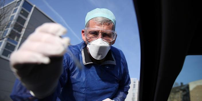 German doctor Michael Grosse takes a sample at a drive-thru testing point in Halle, Germany.