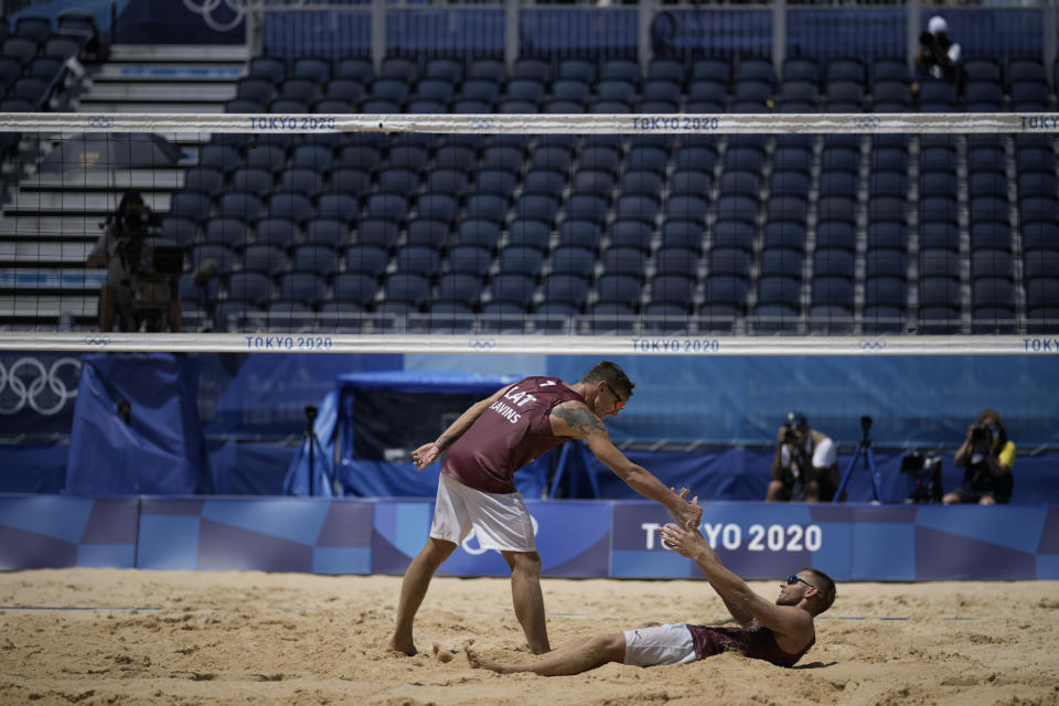 Martins Plavins, center, of Latvia, celebrates with teammate Edgars Tocs, after winning a men's beach volleyball quarterfinal match against Brazil at the 2020 Summer Olympics, Wednesday, Aug. 4, 2021, in Tokyo, Japan. (AP Photo/Felipe Dana)