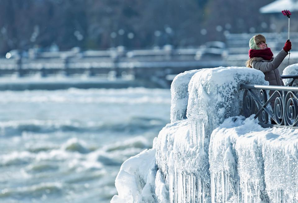 <p>A visitor takes pictures near the brink of the ice-covered Horseshoe Falls in Niagara Falls, Ontario, Canada, January 3, 2018. REUTERS/Aaron Lynett </p>