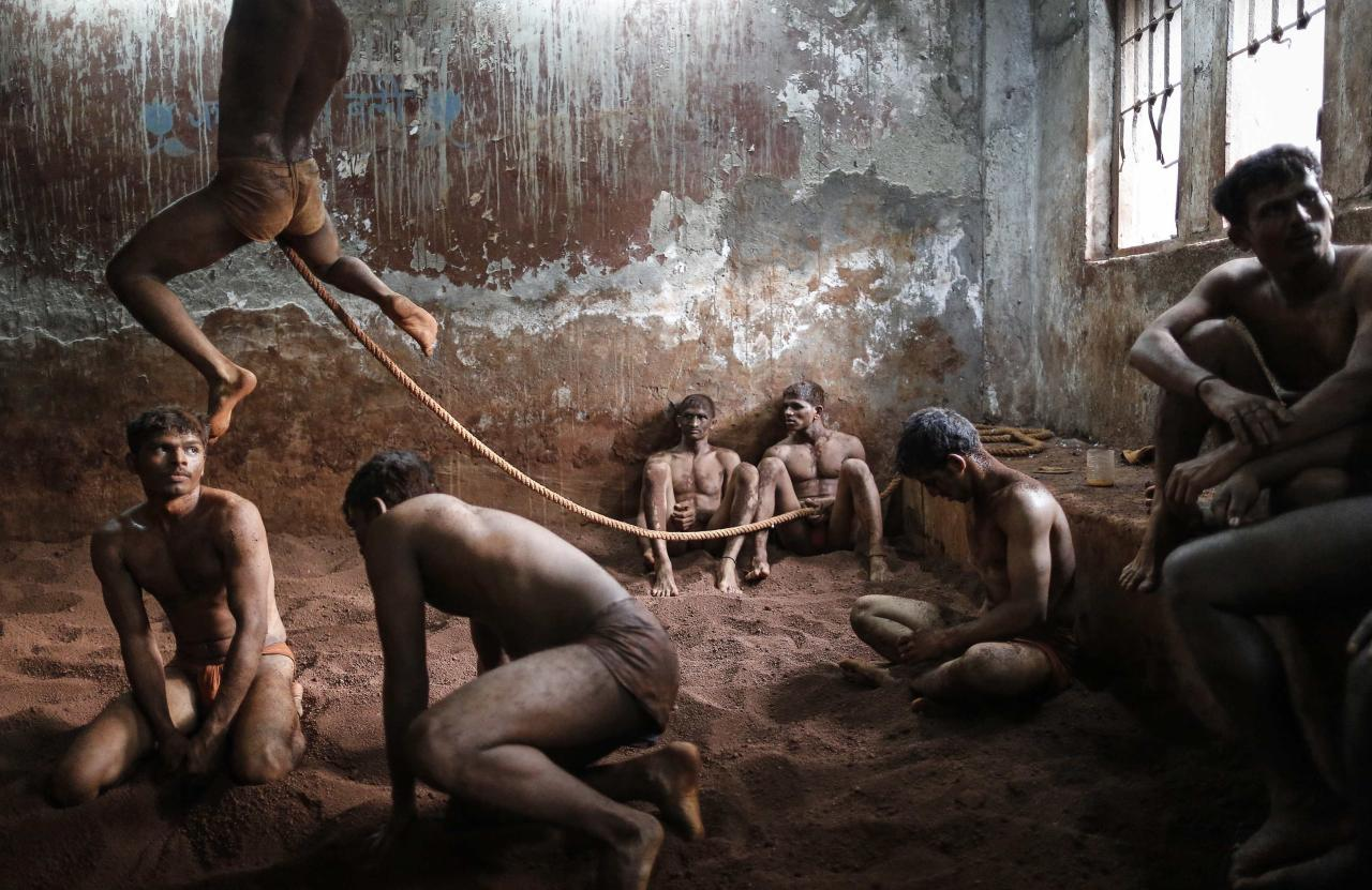 Wrestlers practise as others rest in the mud at a traditional Indian wrestling centre called Akhaara in Mumbai March 4, 2014. Kushti (mud wrestling) is a traditional sport in India but more and more young athletes are now training to wrestle on mats instead of mud to gain access to top international competitions like the Olympic Games or the Commonwealth Games. REUTERS/Danish Siddiqui (INDIA - Tags: SOCIETY SPORT TPX IMAGES OF THE DAY)