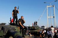 FILE PHOTO: Policemen stand atop military armored vehicles after troops involved in the coup surrendered on the Bosphorus Bridge in Istanbul