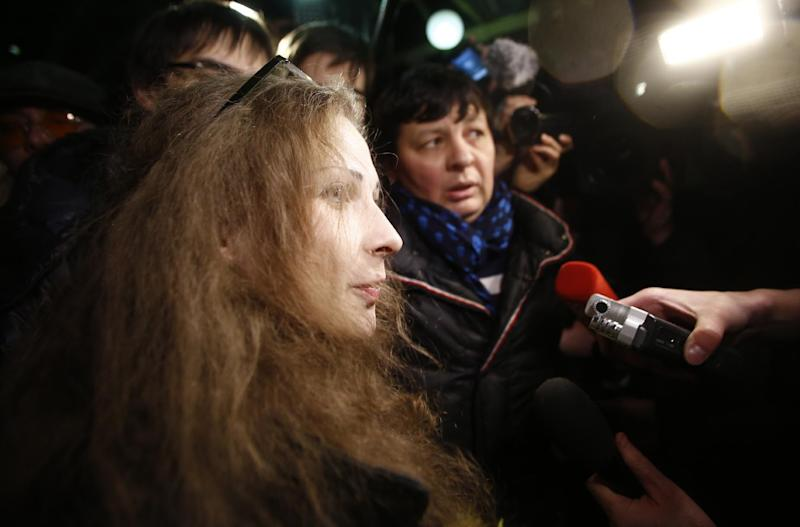 CORRECTS TO PUNK BAND - Member of Russian punk band Pussy Riot, Maria Alekhina, speaks to the media while leaving a train upon her arrival in Moscow, Russia, late Monday, Dec. 23, 2013. Two jailed Pussy Riot members, Alekhina and Nadezhda Tolokonnikova, were released following an amnesty law that both described as a Kremlin public relations stunt ahead of the Winter Olympics. (AP Photo/Denis Tyrin)