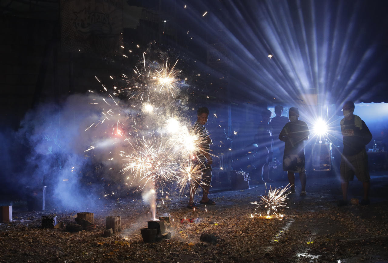 Filipinos stand beside fireworks as they celebrate the coming of the New Year early Wednesday, Jan. 1, 2020 in Manila, Philippines. Filipinos welcome the New Year with noise and firecrackers in the belief that this will drive away bad spirits and bring in good luck. (AP Photo/Aaron Favila)